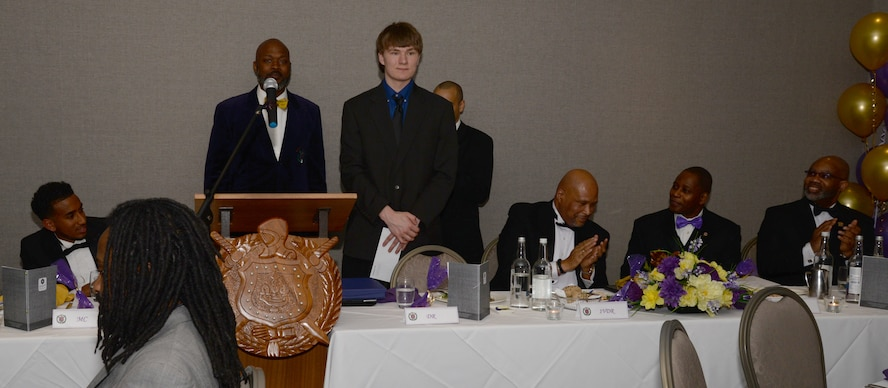 A RAF Lakenheath High School student, center, is awarded an $800 scholarship April 18, 2017, for his submission to an essay contest awarded by the Omega Psi Phi Fraternity Inc., at a banquet in Birmingham, England. Sitting at the head table were district representatives and leaders of the fraternity. The evening was held to celebrate the fifth anniversary of the Chi Mu Mu chapter in the U.K. (U.S. Air Force photo by Senior Airman Justine Rho)