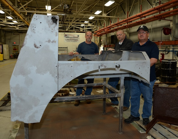 From left are David Tucker, heavy mobile equipment mechanic; Jody Nesbitt, project officer and Robert Guzman, planner estimator; all with Marine Depot Maintenance Command, as they pose April 17 with the cab of a World War II, Suspension Unit-Cab Over Engine Prime Mover, 4x4 Cargo Truck, which is being restored for the National Museum of the Marine Corps.