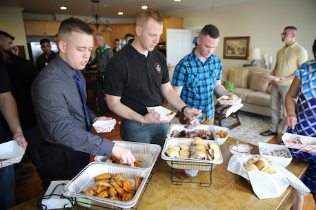 Members of the 2nd Marine Aircraft Wing Band share a meal during a gathering at Marine Corps Air Station Cherry Point NC, March 22, 2017. Brig. Gen. Matthew Glavy hosted the gathering to also present the members of the band with The Colonel George S. Howard Citation of Musical Excellence for Military Concert Bands, Colonel George S. Howard Citation of Musical Excellence for Military Concert Bands and the Live Performance of the Year Award. The 2nd MAW band holds a reputation of professional excellence as they dedicate countless hours to both music and the community. Glavy is the commanding general of 2nd MAW. (U.S. Marine Corps photo by Sgt. N.W. Huertas/ Released)