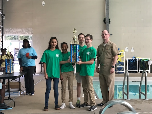 SERMC Commanding Officer, Capt. Dave Gombas, (right) stands with the winning middle school team from Mayport Coastal Sciences Middle School. Students participating in SeaPerch learn important engineering and design skills while exploring naval architecture and ocean engineering principles.