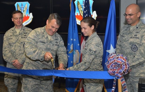 Brig. Gen. Peter Lambert, director of intelligence, Headquarters Air Combat Command, and Airman 1st Class Maggie, the youngest Airman assigned to the CTIC, 35th Intelligence Squadron, open the Cyberspace Threat Intelligence Center during the ribbon cutting ceremony Apr. 10. (U.S. Air Force photo by Lori Bultman)