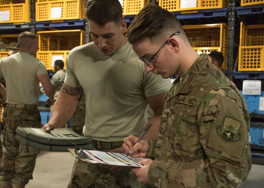 Airman 1st Class Brent Downs, a 386th Expeditionary Logistics Readiness Squadron distribution journeyman, left, issues an improved outer tactical vest to Airman 1st Class Alex Gardner, a traffic management office journeyman, at an undisclosed location in Southwest Asia April 19, 2017. Working at the expeditionary theater distribution center here requires careful attention to detail to ensure forward deployers receive necessary items. (U.S. Air Force photo/Staff Sgt. Andrew Park)