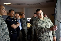 """1st Lt. Conor Melanson, 460th Security Forces Squadron operations officer, breaks down base defense capabilities to Nicholas Metz, Aurora chief of police, and George """"Skip"""" Now, Aurora city manager, April 19, 2017, on Buckley Air Force Base, Colo. By showing Buckley AFB's capabilities, 460th SFS is able to show the types of scenarios which they might need assistance from local authorities. (U.S. Air Force photo by Airman First Class Holden. S. Faul/Released)"""