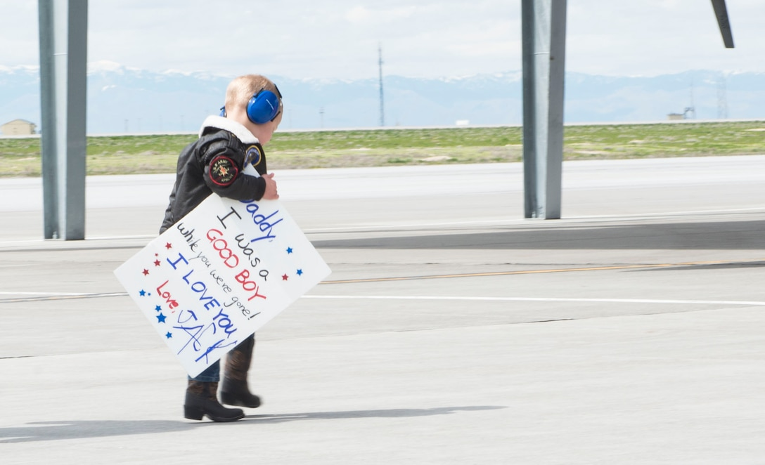 A reunited family embraces during a homecoming of deployed members, April 12, 2017, at Mountain Home Air Force Base, Idaho. More than 5,000 munitions were dropped on ISIS targets in support of Air Forces Central Command. (U.S. Air Force photo by Senior Airman Malissa Lott/Released)