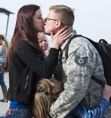 A reunited family embraces during a homecoming of deployed members, April 12, 2017, at Mountain Home Air Force Base, Idaho. More than 5,000 munitions were dropped on ISIS targets in support of Air Forces Central Command. (U.S. Air Force photo by Airman Alaysia Berry/Released)