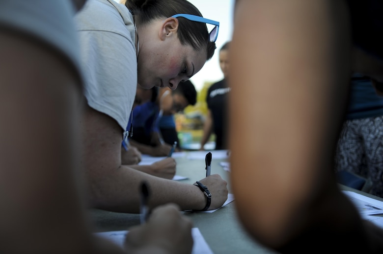 Tech. Sgt. Pamela Mericle, a cyber transport craftsman with the 11th Special Operations Intelligence Squadron, signs up for a 5-kilometer  run at Hurlburt Field, Fla., April 19, 2017. The 5k was held in observance of Sexual Assault Prevention and Awareness Month. (U.S. Air Force photo by Airman 1st Class Dennis Spain)