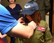 Maddy Hunt gets her pilot wings pinned on by her father, Jay Hunt during the Pilot for a Day Program at Altus Air Force Base Oklahoma, April 14, 2017. The Pilot for a Day Program allows a child with a serious illness to tour the base and experience multiple aspects of Air Force life. (U.S. Air Force photo by SrA. Megan E. Myhre/Released)