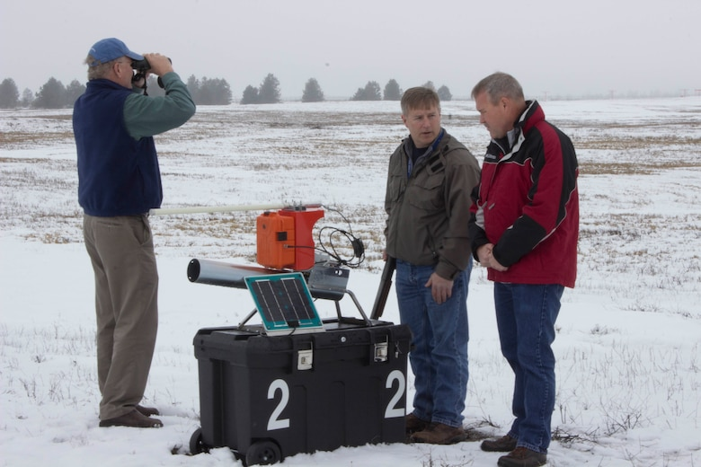 From left, Kevin Porteck, AFCEC natural resources subject matter expert, looks for birds while Dan Paulus, center, pest management foreman for Fairchild Air Force Base, Washington, and Don Teig, AFCEC entomologist and subject matter expert, discuss the usage of the propane air cannon for bird deterrence on the airfield at the base March 9, 2017. (U.S. Air Force photo/Susan Lawson).
