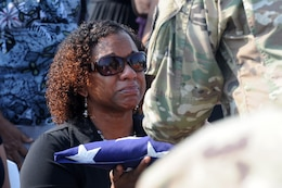 Deshana Pandy receives a folded American flag from Command Sgt. Major Angel Rivera at a funeral detail for her father, 22-year Army veteran Master Sgt. David Daniel Alexander Pandy Jr., at a cemetery in Ladyville, Belize on March 30, 2017. The sergeant major is a reservist from Puerto Rico's 210th Regional Support Group assigned to Beyond the Horizon 2017-Belize, a U.S.-Belize partnership exercise encompassing three health care events and five construction projects designed to improve the health and education infrastructure of Belizean communities.