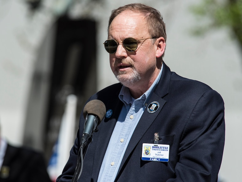 """DAYTON, Ohio (04/2017) -- Jeff Thatcher, son of Doolittle Raider, Staff Sgt. David Thatcher, gives remarks at the National Museum of the United States Air Force April 18, 2017. The memorial service, including a wreath laying, honored the 75th anniversary of the Doolittle Tokyo Raid in which 80 volunteers used 16 B-25 bombers to strike the Japanese mainland from the USS Hornet aircraft carrier, turning the tide of World War II. The ceremony included two flyovers of B-25 bombers, one in the missing man formation, and a B-1B bomber flyover, one of which had been rechristened the """"Ruptured Duck"""" in a ceremony the day before. Staff Sgt. Thatcher was a crew member on the original Ruptured Duck, during the Doolittle Raid. (U.S. Air Force photo by Ken LaRock)"""