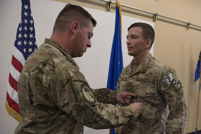 Maj. Michael Warren, 824th Base Defense Squadron commander, pins an achievement medal on Staff Sgt. David Green, 824th BDS fireteam leader, April 10, 2017, at Moody Air Force Base, Ga. Green received the medal for his act of heroism when he helped a trapped victim during an off-base vehicle incident. (U.S. Air Force photo by Airman 1st Class Lauren M. Sprunk)
