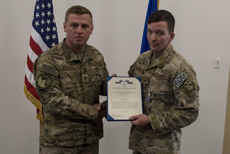Maj. Michael Warren, 824th Base Defense Squadron commander, awards Staff Sgt. David Green, 824th BDS fireteam leader, with an achievement medal, April 10, 2017, at Moody Air Force Base, Ga. Green received the medal for his act of heroism when he helped a trapped victim during an off-base vehicle incident. (U.S. Air Force photo by Airman 1st Class Lauren M. Sprunk)