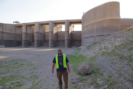 Jason Foust, deputy construction manager for the grouting project at Mosul Dam, stands by the spillway gates Oct. 22, 2016 where they drew drawn down to alleviate pressure during the work. Foust has since returned to the U.S. Army Corps of Engineers Nashville District where he is project engineer at the Kentucky Lock Addition Project in Grand Rivers, Ky. (Photo by Charlie Krolikowski)
