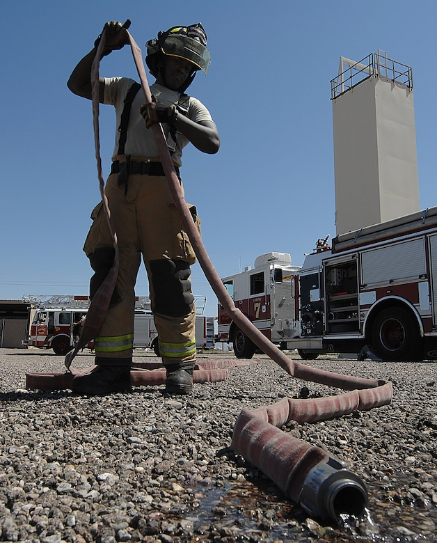U.S. Air Force Senior Airman Haji Stewart, 355th Civil Engineering Squadron firefighter, drains a fire hose of excess water after a fire attack drill at Davis-Monthan Air Force Base, Ariz., April 19, 2017. The 355th CES Fire Emergency Services recently received Accredited Agency status from the Commission on Fire Accreditation International. (U.S. Air Force photo by Airman 1st Class Frankie Moore)