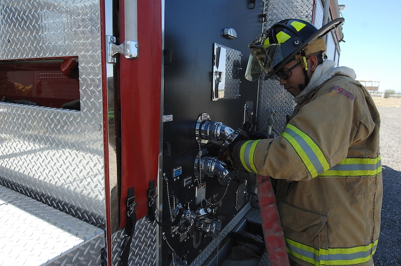 U.S. Air Force Senior Airman Jonathan Bautista, 355th Civil Engineering Squadron firefighter, connects and tightens a fire hose to a fire engine at Davis-Monthan Air Force Base, Ariz., April 19, 2017. D-M has a range of fire engines that can hold between 500 to 3,300 gallons of water. (U.S. Air Force photo by Airman 1st Class Frankie Moore)