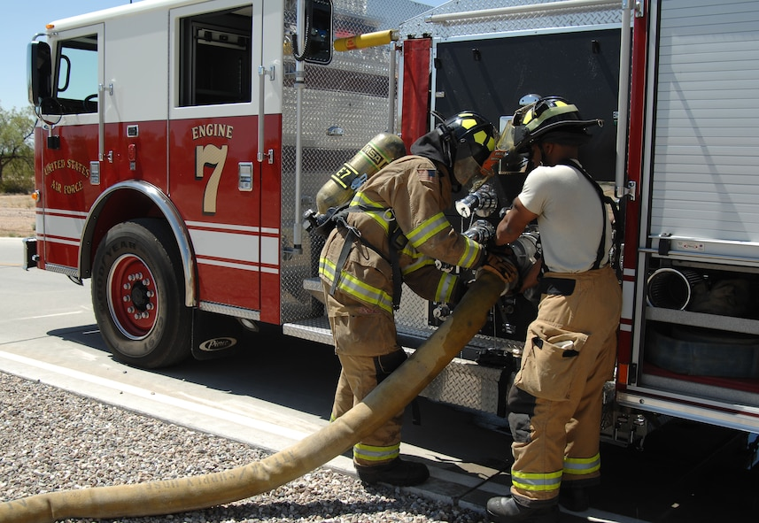 U.S. Air Force Airman 1st Class DeAndre Ward and Jacob Williams, 355th Civil Engineering Squadron firefighters, help each other connect a hose to a fire engine during fire hydrant training outside of at Davis-Monthan Air Force Base, Ariz., April 19, 2017. D-M fire fighters continuously train throughout the week in order to keep their skills honed. (U.S. Air Force photo by Airman 1st Class Frankie Moore)