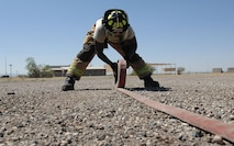 U.S. Air Force Senior Airman Haji Stewart, 355th Civil Engineering Squadron firefighter, rolls up a fire hose after a fire attack drill at Davis-Monthan Air Force Base, Ariz., April 19, 2017. The 355th CES Fire Emergency Services recently received Accredited Agency status from the Commission on Fire Accreditation International. (U.S. Air Force photo by Airman 1st Class Frankie Moore)