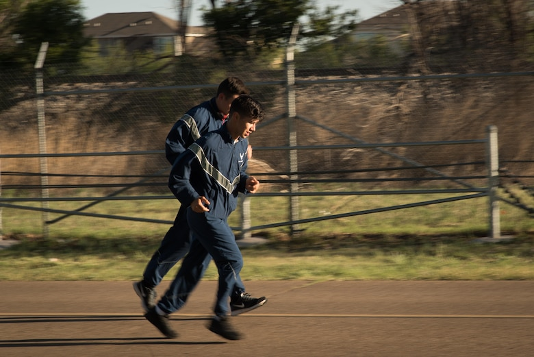 Two Airmen run down North Perimeter Road during the Arbor Day and Earth Day 5K fun run at Unity Park on Cannon Air Force Base, NM, April 19, 2017. The run was the first of three events in celebration of Earth Day and Arbor Day. (U.S. Air Force photo by Staff Sgt. Michael Washburn/Released)