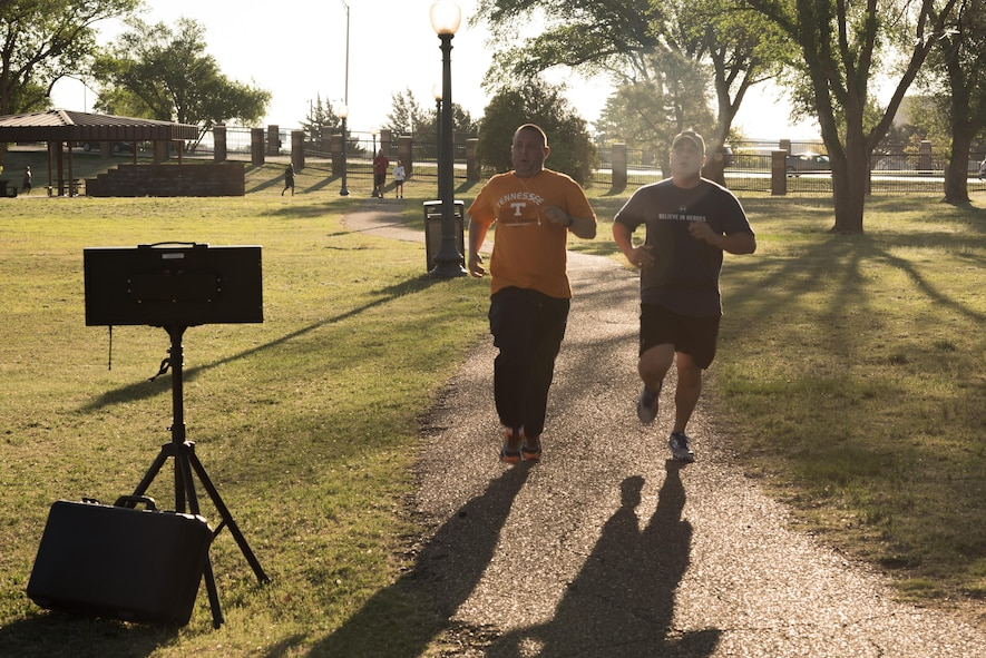Two participants in the Arbor Day and Earth Day 5K fun run cross the finish line at Unity Park on Cannon Air Force Base, NM, April 19, 2017. The fastest time for men was 17:59 and the fastest time for women was 23:29. (U.S. Air Force photo by Staff Sgt. Michael Washburn/Released)