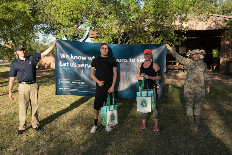 (Middle left) Ilan Serrano, and (middle right) Tayler Wyttenbach, pose for a picture after finishing the Arbor Day and Earth Day 5K fun run as the fastest male and female at Unity Park on Cannon Air Force Base, NM, April 19, 2017. Serrano finished the race in 17:59 and Wyttenbach finished in 23:29. (U.S. Air Force photo by Staff Sgt. Michael Washburn/Released)