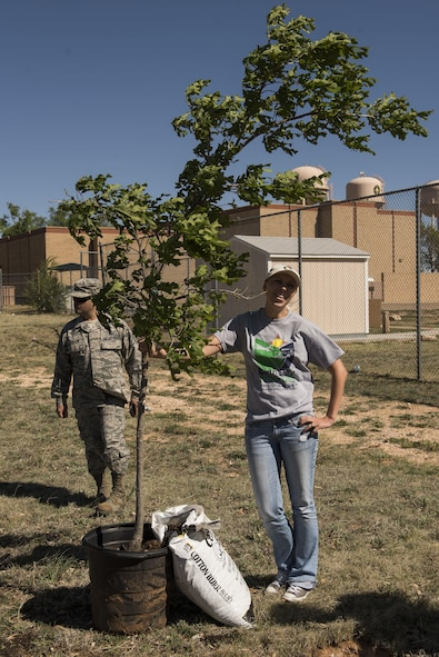 Ola Kirk, 27th Special Operations Civil Engineer Squadron Environmental Office, poses for a photo with the ceremonial tree during the Arbor Day and Earth Day tree planting ceremony at the Youth Center on Cannon Air Force Base, NM, April 19, 2017. With the planting of the tree, April 19 was deemed Arbor Day for Cannon, as decreed by Col. Douglas Gilpin, 27th Special Operations Mission Support Group commander. (U.S. Air Force photo by Staff Sgt. Michael Washburn/Released)