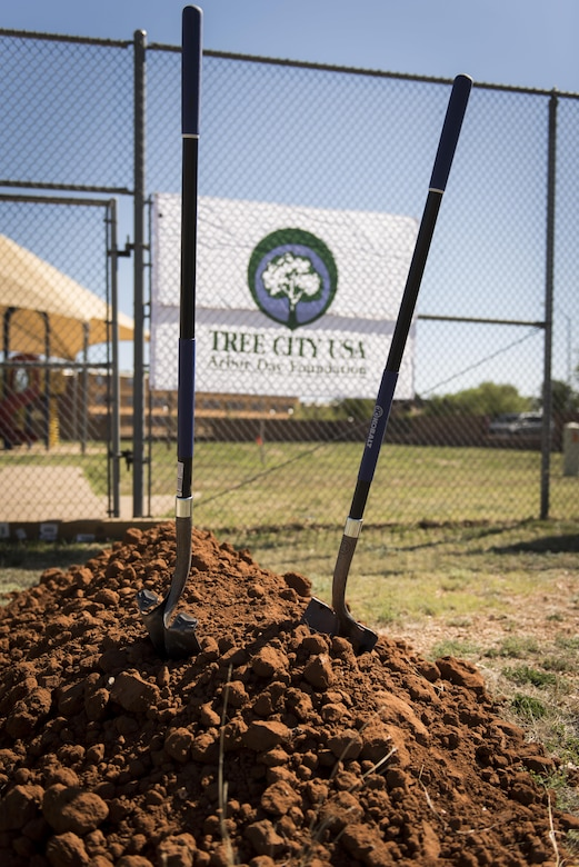 Shovels stick out of a dirt pile at the Arbor Day and Earth Day tree planting ceremony at the Youth Center on Cannon Air Force Base, NM, April 19, 2017. The speaker at the event was Col. Douglas Gilpin, 27th Special Operations Mission Support Group commander, who also threw the first mound of dirt. (U.S. Air Force photo by Staff Sgt. Michael Washburn/Released)