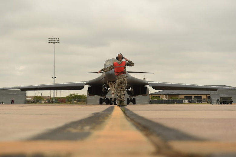 U.S. Air Force Airman 1st Class Chance Barfield, 7th Aircraft Maintenance Squadron crew chief, marshals Maj. Gen. Thomas Bussiere, 8th Air Force commander, toward the runway for his B-1B Lancer familiarization flight at Dyess Air Force Base, Texas, April 19, 2017. During his visit, Bussiere, was given the opportunity to fly in the B-1 to understand the bomber's critical role in security and deterrence while at home and abroad. (U.S. Air Force photo by Airman 1st Class Emily Copeland)