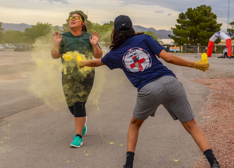 Staff Sgt. Dominique Lindsey, 99th Medical Operations Squadron mental health technician, throws yellow powder on an Airman during the 5k Color Run/Walk, April 7, 2017 at Nellis Air Force Base, Nev. Each color used represented a different agency around base. (U.S. Air Force photo by Airman 1st Class Andrew D. Sarver/ Released)