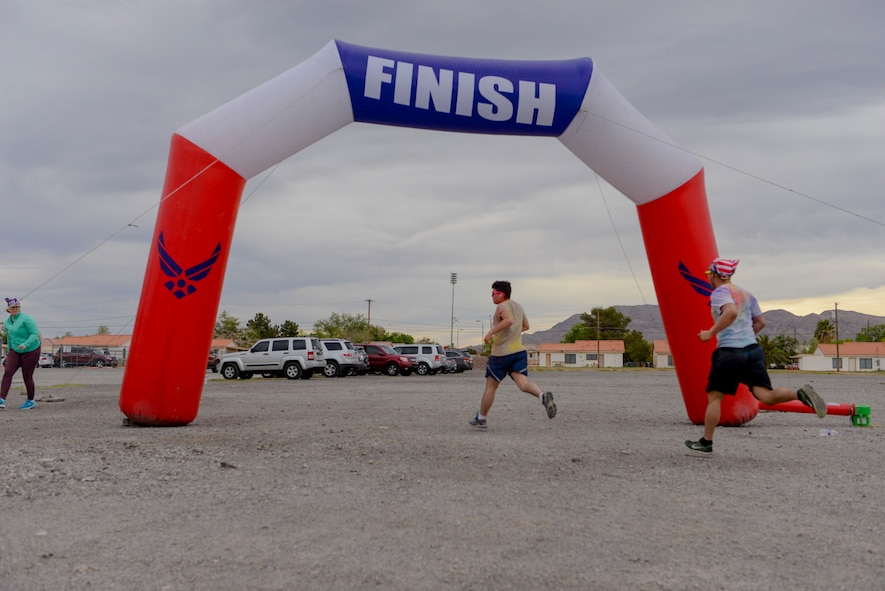 Airmen cross the finish line at the 5k Color Run/Walk, April 7, 2017, at Nellis Air Force Base, Nev. Multiple base agencies set up stands at the finish line to promote awareness and offer further information for Airmen and their families. (U.S. Air Force photo by Airman 1st Class Andrew D. Sarver/ Released)