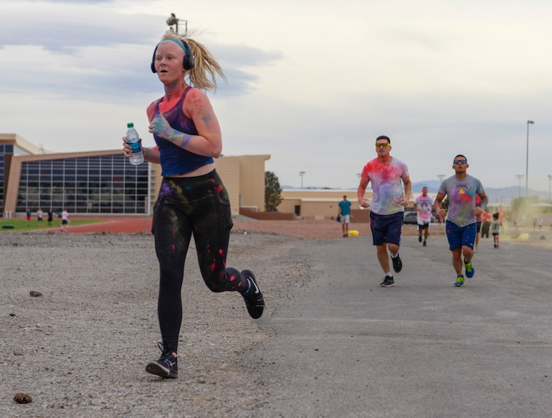 Senior Airman Mikaley Kline, 99th Air Base Wing Public Affairs photojournalist, sprints ahead of other Airmen at the 5k Color Run/Walk, April 7, 2017, at Nellis Air Force Base, Nev. This is the second 5k Color Run/Walk Kline has participated in at Nellis AFB. (U.S. Air Force photo by Airman 1st Class Andrew D. Sarver/ Released)