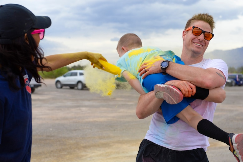 Master Sgt. Briand Daubert, a 414th Combat Training Squadron personnel recovery division member, carries his son to get covered with yellow powder during the 5k Color Run/Walk, April 7, 2017, at Nellis Air Force Base, Nev. Daubert and his family participated in the run which promoted Comprehensive Airmen Fitness. (U.S. Air Force photo by Airman 1st Class Andrew D. Sarver/ Released)