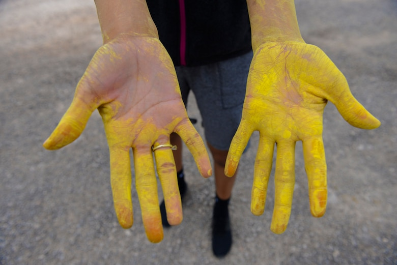 Staff Sgt. Dominique Lindsey, 99th Medical Operations Squadron mental health technician, shows her hands during the 5k Color Run/Walk, April 7, 2017, at Nellis Air Force Base, Nev. The 5k Color Run/Walk raised awareness for Comprehensive Airman Fitness. (U.S. Air Force photo by Airman 1st Class Andrew D. Sarver/ Released)