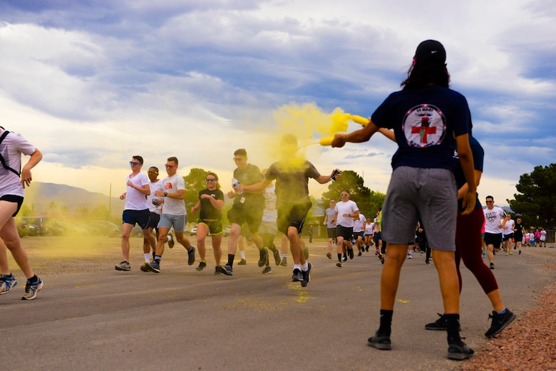 Staff Sgt. Dominique Lindsey, 99th Medical Operations Squadron mental health technician, showers Airmen with yellow powder at the 5k Color Run/Walk, April 7, 2017, at Nellis Air Force Base, Nev. The 5k Color Run/Walk participants were doused with several colors that represented different base agencies around Nellis AFB. (U.S. Air Force photo by Airman 1st Class Andrew D. Sarver/ Released)