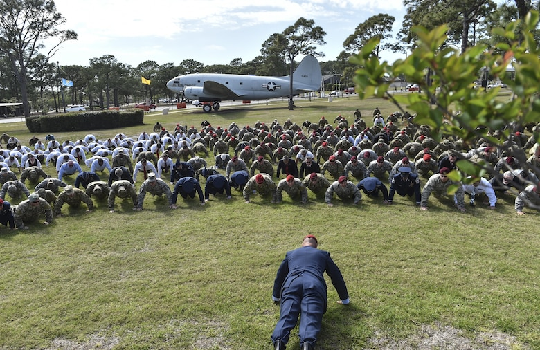 "Col. Michael E. Martin, the commander for the 24th Special Operations Wing, leads Airmen in ""Memorial Pushups"" honoring the fallen following a dual Air Force Cross ceremony, April 20, 2017, at Hurlburt Field, Fla. For the first time in Air Force history, two Airmen were simultaneously awarded the service's highest medal for valorous action in combat. Master Sgt. (Ret.) Keary Miller, a retired Special Tactics pararescueman from the Air National Guard's 123rd Special Tactics Squadron, and Chris Baradat, a combat controller since separated, both received Silver Star medals for their actions in combat, which were upgraded after a service-wide review. (U.S. Air Force photo by Senior Airman Ryan Conroy)"