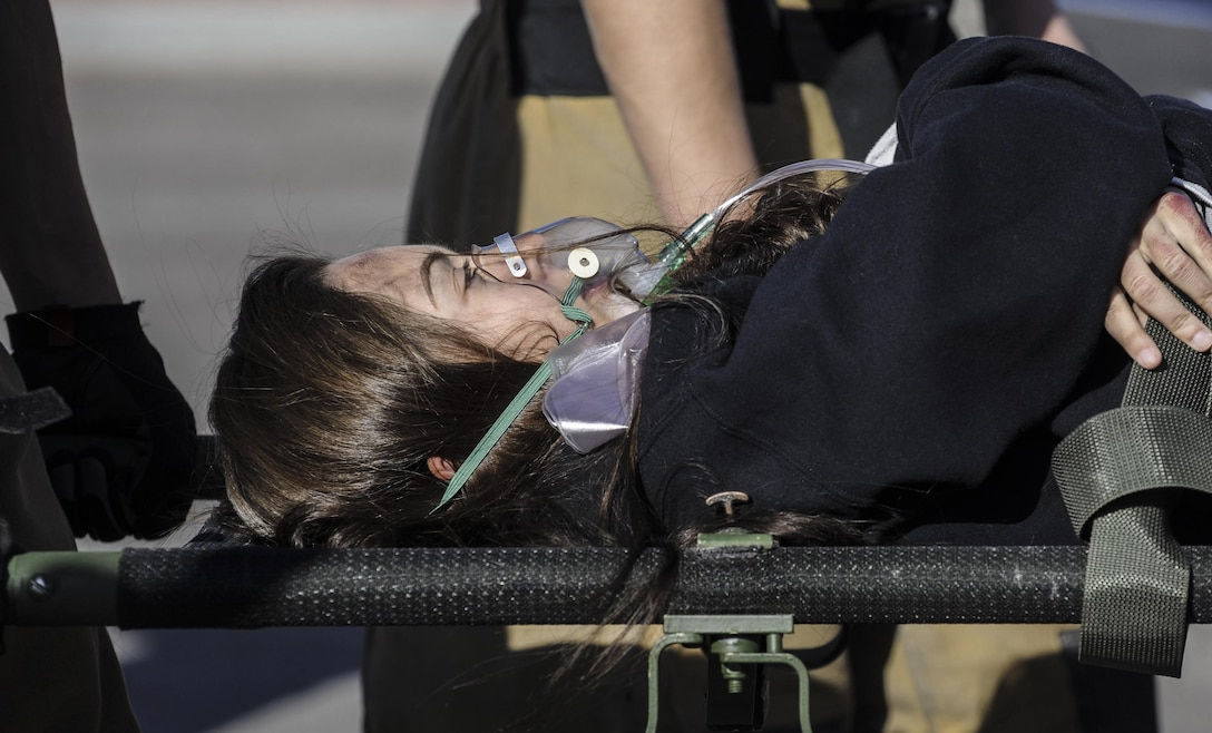 A simulated victim breaths into a mask during the Major Accident Response Exercise at Nellis Air Force Base, Nev., April. 13, 2017. The participants included Wing Inspection Team members, Scene Controllers for additional safety, and volunteers simulating victims and witnesses for the exercise. (U.S. Air Force photo by Senior Airman Kevin Tanenbaum/Released)