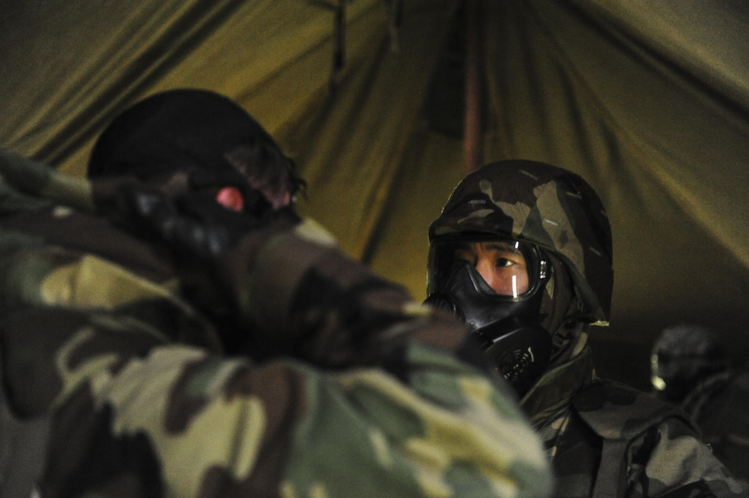 Airmen stationed at Hickam Field check each other's Mission Oriented Protective Posture (MOPP) gear for an exercise scenario during Exercise TROPIC THUNDER 2017 (XTT17), at Wheeler Army Airfield, Hawaii, April 20, 2017.  XTT17 is a two part full spectrum readiness exercise hosted by the 15th Wing to test the individual, organizational and expeditionary readiness of the Airmen stationed at Joint Base Pearl Harbor-Hickam. (U.S. Air Force photo by Tech. Sgt. Heather Redman)