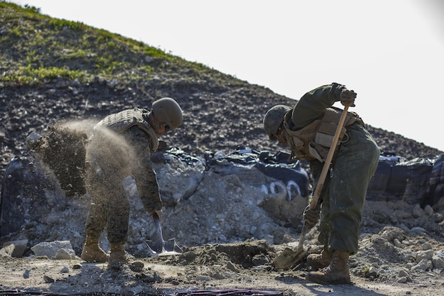 U.S. Marine Corps Gunnery Sgt. Myron Sato, left, the combat engineer staff noncommissioned officer in charge for Marine Wing Support Squadron (MWSS) 171, and Pfc. Jason Taylor, right a combat engineer with MWSS-171, shovel dirt and mud during airfield damage and repair training at Marine Corps Air Station Iwakuni, Japan, April 19, 2017. The ADR training required Marines to utilize their skill set to tactically and proficiently fix any anomalies to a simulated damaged airfield. The training focused on becoming more efficient in situations that may require Marines to act in real-world scenarios to maintain the tempo of aircraft operations. (U.S. Marine Corps photo by Lance Cpl. Joseph Abrego)