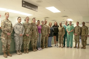 Army Capt. Kelly Elmlinger, a military nurse and cancer survivor, center, visits with staff members at William Beaumont Army Medical Center's surgical ward at Fort Bliss, Texas, where she shared her experiences during her fight with synovial sarcoma, a rare soft-tissue cancer, April 6, 2017. Elmlinger, who is coaching and mentoring wounded warriors during this year's Department of Defense Warrior Games, visited with staff members to help them understand the impact medical staff can have on patients. Army photo by Marcy Sanchez