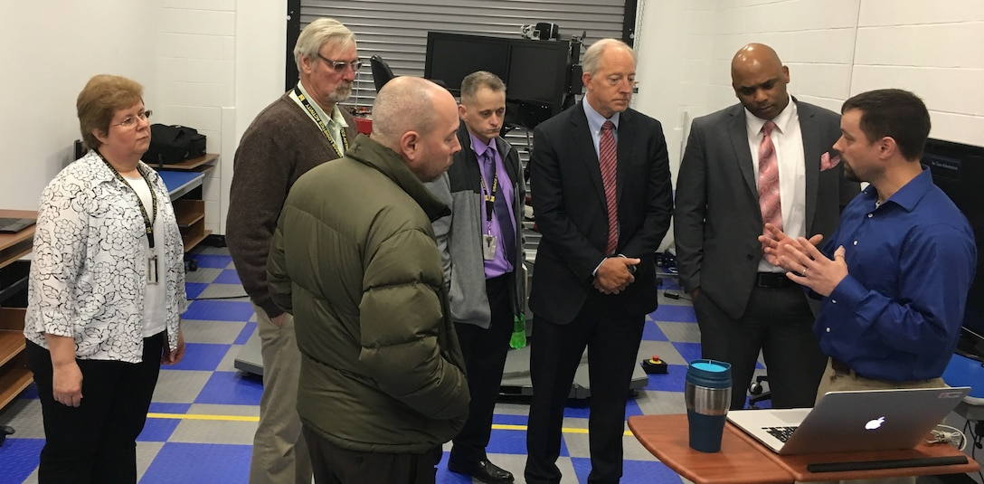 Additionally, the visitors were provided an overview of CRREL's Simulation-bAsed Vehicle Control Training Simulator by Mechanical Engineer Mike Parker. Parker and other engineers have worked to create simulated driver training for Soldiers to greatly reduce accidents through enhanced vehicle control training with this simulator. Accompanying the group, on far left, is Hanover onsite District Logistics Manager Betty O'Donnell