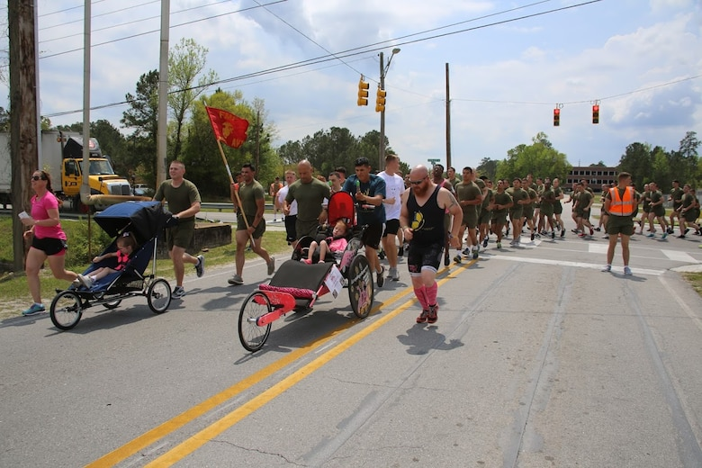 Marines push athlete riders along side other Marines during a formation run at Marine Corps Air Station New River, N.C., April 13, 2017. More than 220 Marines assigned to Marine Aviation Logistics Squadron 26, Marine Aircraft Group 26, 2nd Marine Aircraft Wing  came together to lend their feet to disabled children for an Ainsley's Angels East Carolina chapter event. The unit participated in the event to show their support for the local community and share their Espirit De Corps. ( U.S. Marine Corps photo by Sgt. N.W. Huertas/ Released)