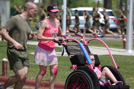 Marines run along side volunteer runners during a formation run at Marine Corps Air Station New River, N.C., April 13, 2017. More than 220 Marines assigned to Marine Aviation Logistics Squadron 26, Marine Aircraft Group 26, 2nd Marine Aircraft Wing  gathered to run with disabled children as part of an Ainsley's Angels East Carolina chapter event at the air station. Ainsley's Angels is an organization that focuses on providing children with disabilities the oportunity to be included in runs that range in distances from 5k up to 50k. Volunteers are assigned as angels to push the athlete riders and cross the finish line. ( U.S. Marine Corps photo by Sgt. N.W. Huertas/ Released)