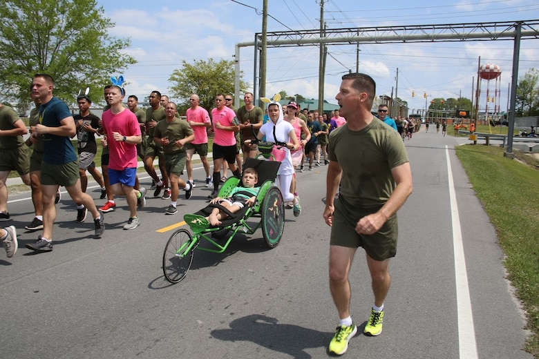Marines call cadences during a formation run at Marine Corps Air Station New River, N.C., April 13, 2017. More than 220 Marines assigned to Marine Aviation Logistics Squadron 26, Marine Aircraft Group 26, 2nd Marine Aircraft Wing  gathered to run with disabled children as part of an Ainsley's Angels East Carolina chapter event at the air station. Many Marines dressed in easter themed costumes as a way to celebrate the season and show their support to the organization. ( U.S. Marine Corps photo by Sgt. N.W. Huertas/ Released)