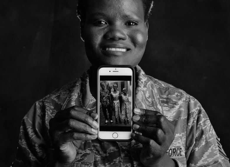Staff Sgt. Martha Otto, a former South-Sudanese refugee, holds a photo of her nephew and nieces, whom, like Otto years ago, fled their civil war-torn country of South Sudan in search of safety from Joseph Kony's Lord Resistance Army. The 86th Logistics Readiness Squadron training manager recently financially assisted her family out of a North Ugandan refugee camp and into boarding school and is passionate about sharing her story to help others. (U.S. Air Force photo by Staff Sgt. Nesha Humes)