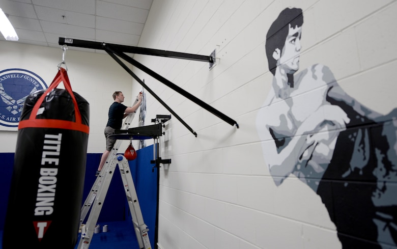 Ian Mangum, 42nd Force Support Squadron Family Camp reservation specialist, paints a mural at the Gunter Air Force Base Gym, April 14, 2017. Mangum has put in more than 100 hours of work into painting the murals for the newest boxing gym. (U.S. Air Force photo/Senior Airman Tammie Ramsouer)