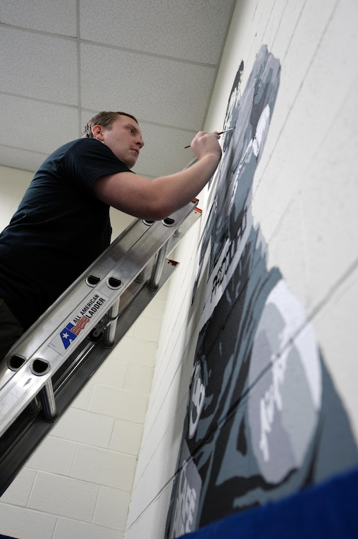 Ian Mangum, 42nd Force Support Squadron Family Camp reservation specialist, paints a mural at the Gunter Air Force Base Gym, April 14, 2017. Mangum used more than five paints ranging from white to black. (U.S. Air Force photo/Senior Airman Tammie Ramsouer)