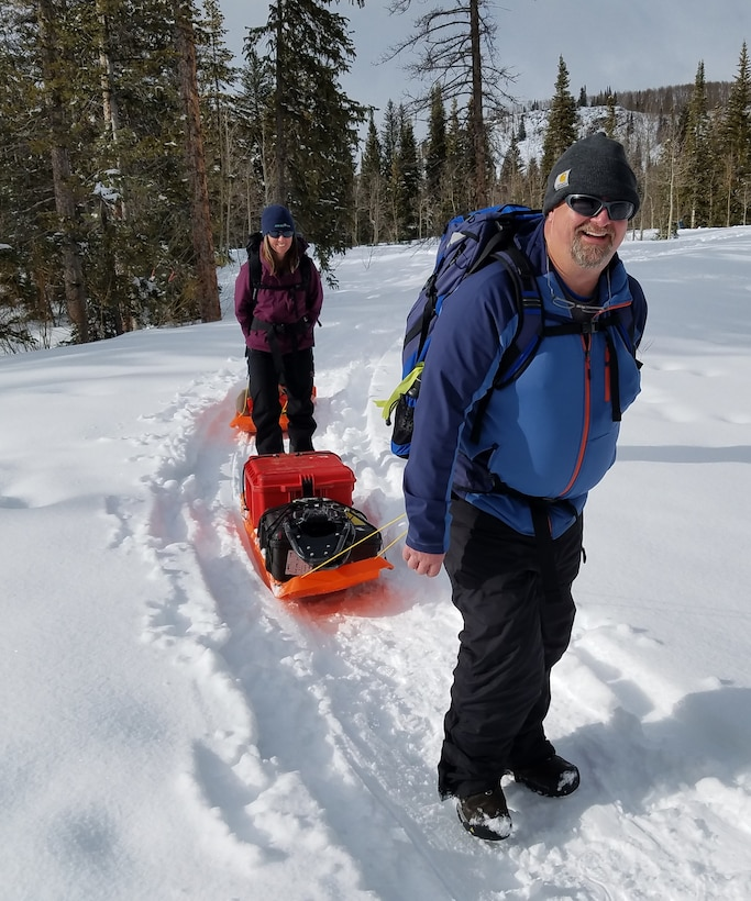 CRREL Researchers Dr. Carrie Vuyovich (back) and Art Gelvin (front) use sleds to transport the terrestrial laser scanner from the Local-Scale Observation Site. Scans were completed in snow-on and snow-off conditions to determine snow distribution and relate that to other instruments.