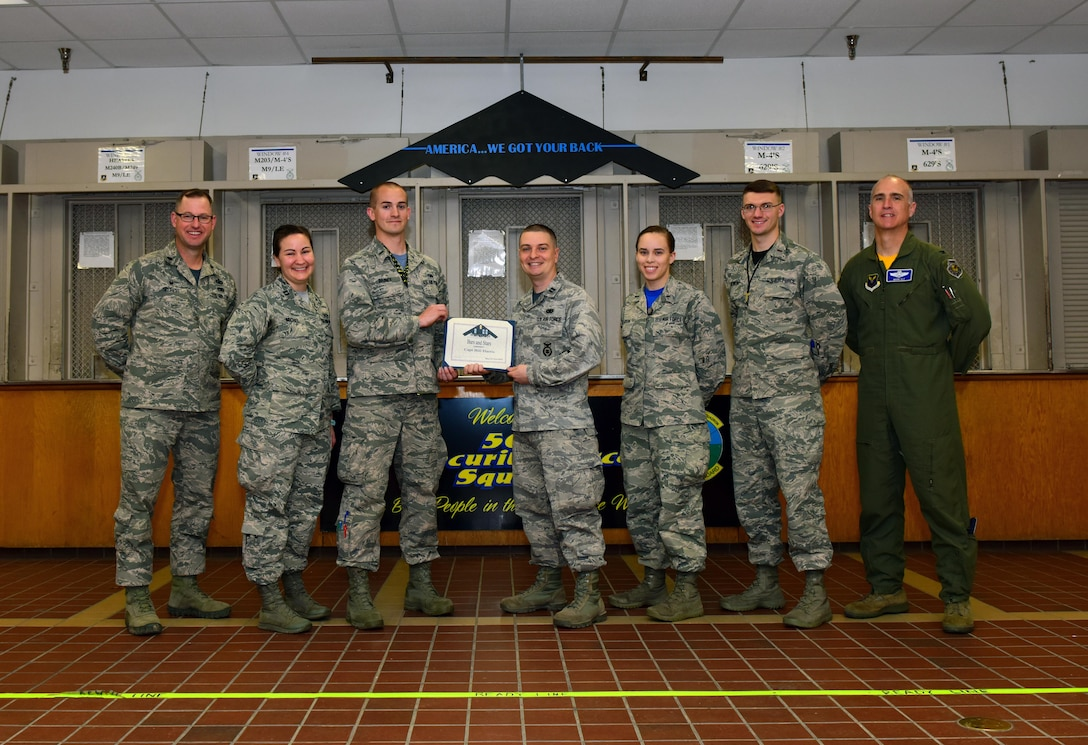 U.S. Air Force Capt. Bill Harris, the 509th Security Forces Squadron logistics officer in charge, center right, receives a Whiteman Company Grade Officer Council (CGOC) Bars and Stars award from members of the CGOC and Col. Mark Ely, the 509th Bomb Wing vice commander, at Whiteman Air Force Base, Mo., April 7, 2017. Harris consistently engaged with his troops and provided them with the resources needed to cope with the loss of a fellow Airman. He also organized his section to provide a weapons and vehicle demonstration to 13 kids from the youth center as part of a local outreach event. (U.S. Air Force photo by Airman 1st Class Jazmin Smith)