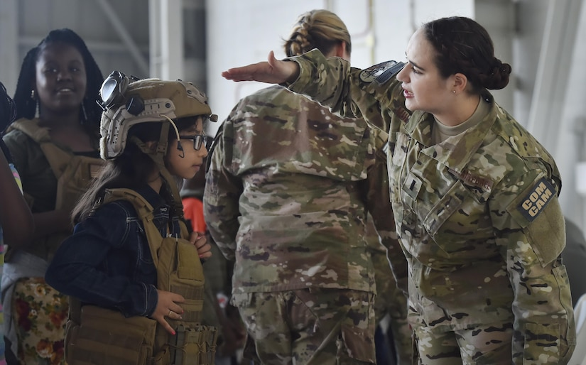 First Lt. Meredith Mulvihill, 1st Combat Camera Squadron, helps a 5th-grade student from Sedgefield Intermediate School don individual protective equipment as part of a career day event at Joint Base Charleston, S.C., April 20, 2017. The students talked to Airmen and participated in various career field specific demonstrations alongside subject matter experts from various units on the installation. Junior Reserve Officer Training Corps members from Fort Dorchester High School, Orangeburg Wilkinson High School, Summerville High School and Military Magnet Academy were also attended the event.
