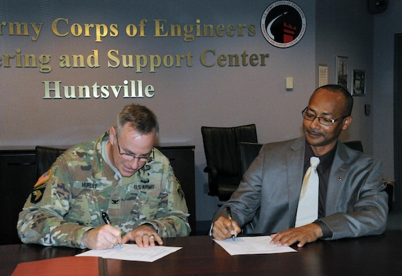 Col. John S. Hurley, commander U.S. Army Engineering Center, Huntsville and Abner Merriweather, president of AFGE Local 1858, place their signatures on Huntsville Center's first collective bargaining agreement April 13.