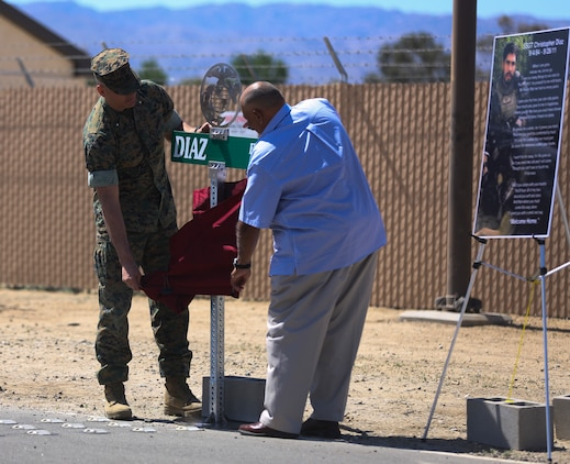 Combat Center Commanding General, Brig. Gen. William F. Mullen III and Salvador Diaz, Staff Sgt. Christopher Diaz's father, unveil the road sign during the renaming ceremony of Calcite Road to Diaz Road, April 14, 2017, aboard the Marine Corps Air Ground Combat Center, Twentynine Palms, Calif. The road was renamed in honor of Staff Sgt. Diaz who made the ultimate sacrifice to help a brother in arms while conducting combat operations in Helmand Province, Afghanistan in support of Operation Enduring Freedom. (U.S. Marine Corps photo by Cpl. Medina Ayala-Lo)